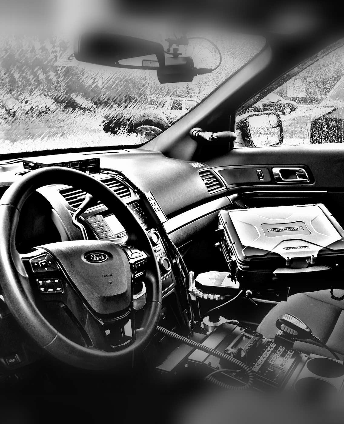 Black and white photo of the interior dashboard of a Police vehicle