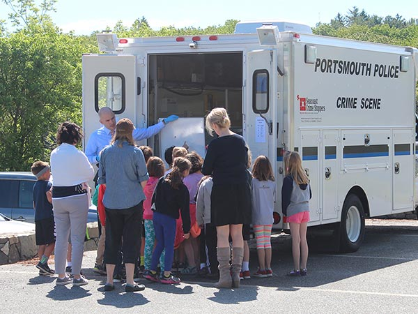 Officer showing a group of students the Police Evidence Van