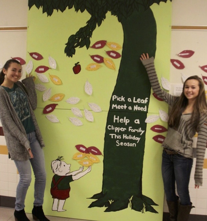 Haley Dewsnap and Lauren Marin standing with the Giving Tree displayed in main foyer at Portsmouth High School