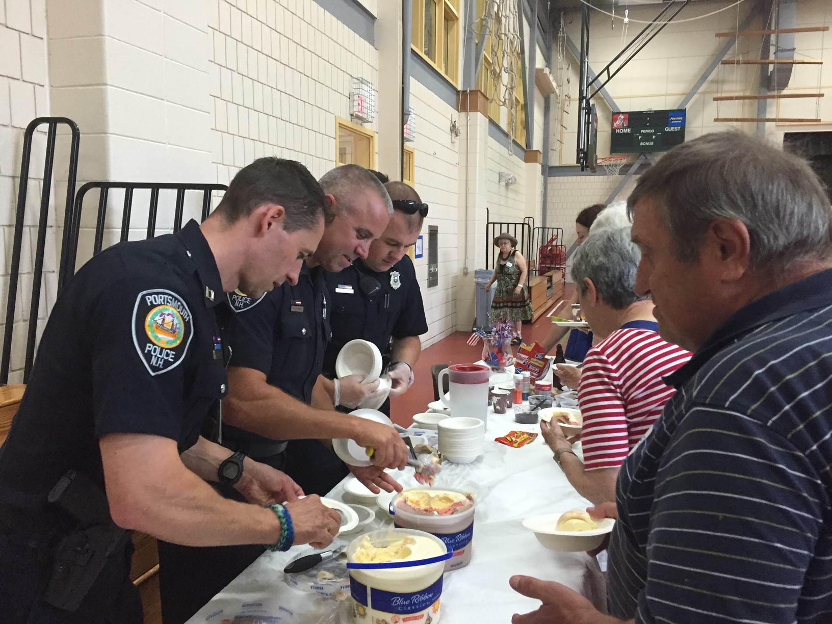 Police officers serve ice cream at the senior cookout
