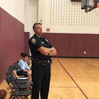 Police Officer watching basketball game