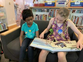 Two children reading in the library