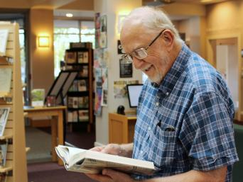 Older man reading in library lobby