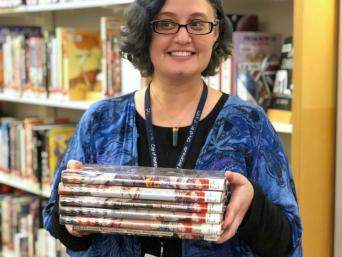 Library staff member with stack of graphic novels